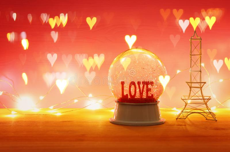 Valentine's day background. Water globe with word LOVE and glitter over the wooden table and pink bakground. Hearts overlay. Valentine's day stock photos