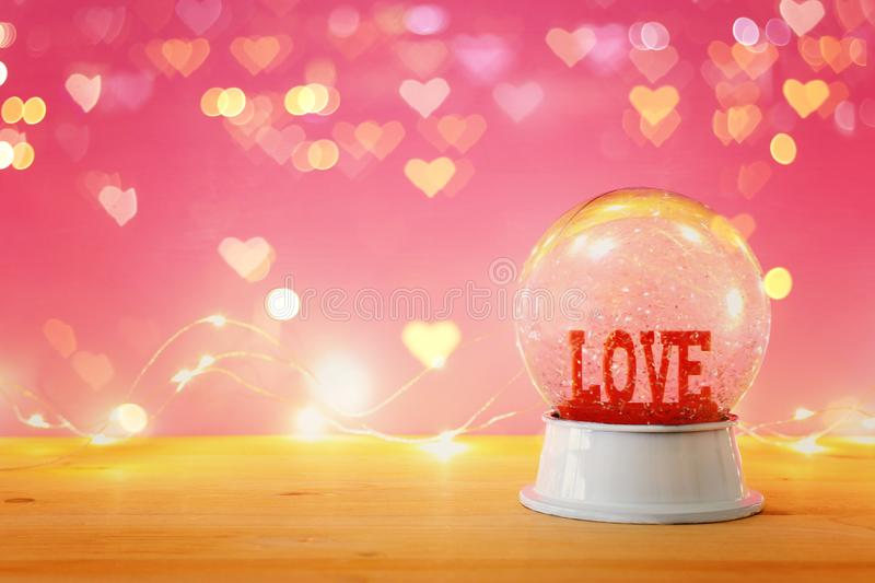 Valentine's day background. Water globe with word LOVE and glitter over the wooden table and pink bakground. Hearts overlay. Valentine's day royalty free stock photography