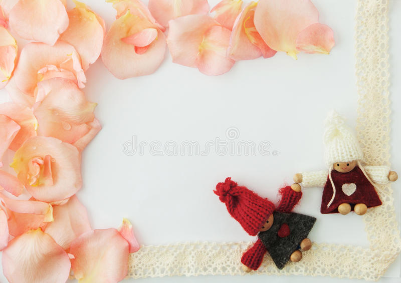 Valentine's day background. White background with soft pink rose. Petals and knitted loving couple man and woman. Valentine, greeting card, blank. your text stock images