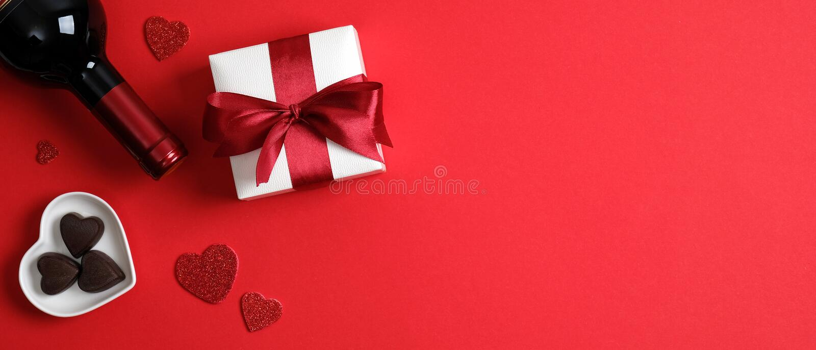 Valentine`s day banner template with wine bottle, valentine gift, heart shaped candies on red background with copy space. Top vie royalty free stock images