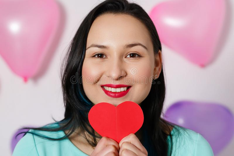 Valentine`s Day. Beautiful young woman with heart in her hands. Young woman with red heart on white background with inflatable stock image