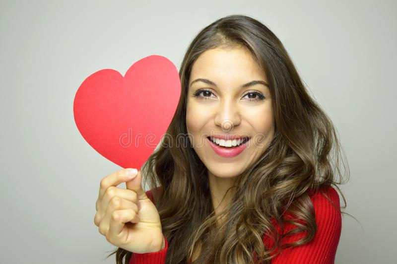 Valentine`s Day. Beautiful young woman in love holding a paper heart and smile at camera on gray background. royalty free stock images