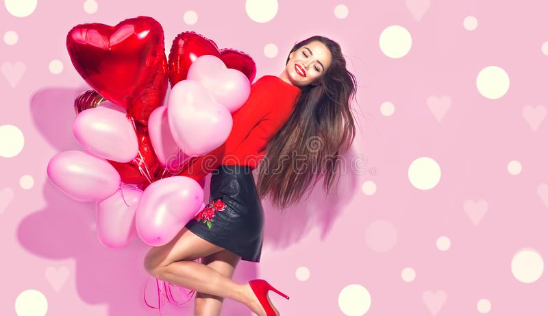 Valentine`s Day. Beauty girl with colorful air balloons having fun. Over pink background royalty free stock image