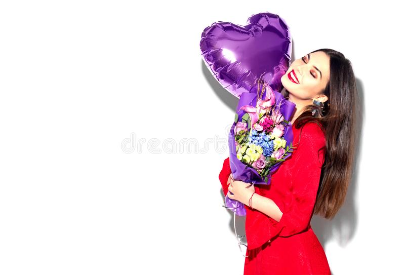 Valentine`s Day. Beauty girl with colorful bouquet of flowers and heart shape air balloon on white background. Beautiful happy young woman stock photography