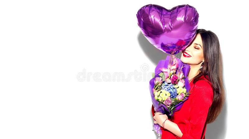 Valentine`s Day. Beauty girl with colorful bouquet of flowers and heart shape air balloon on white background. Beautiful happy young woman royalty free stock images