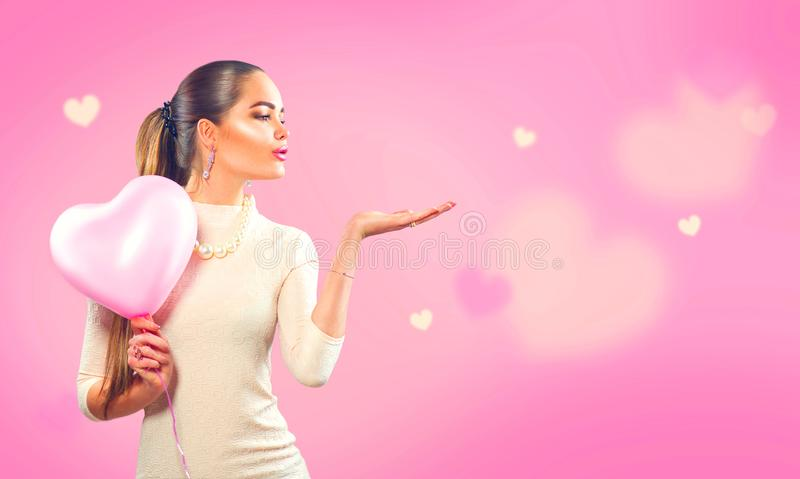 Valentine`s day. Beauty girl with pink heart shaped air balloon pointing hand stock image