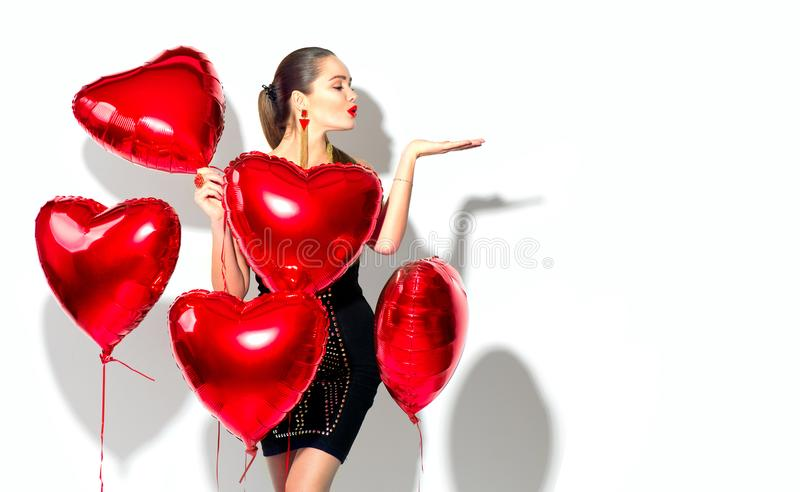Valentine`s Day. Beauty girl with red heart shaped air balloons having fun royalty free stock image