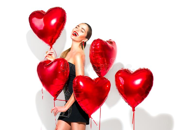 Valentine`s Day. Beauty girl with red heart shaped air balloons having fun royalty free stock images