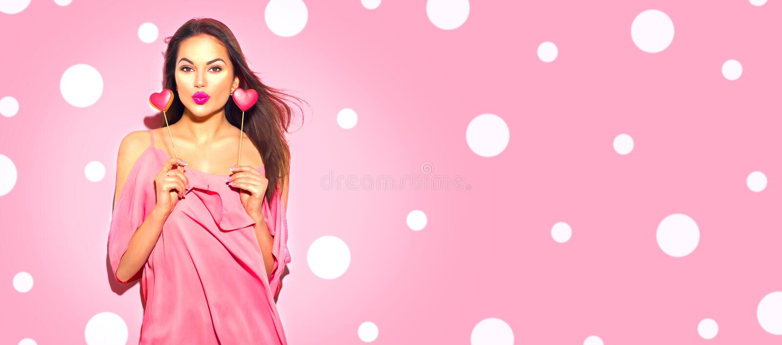Valentine`s Day. Beauty joyful young fashion model girl with Valentine heart shaped cookies. Isolated on pink background stock image