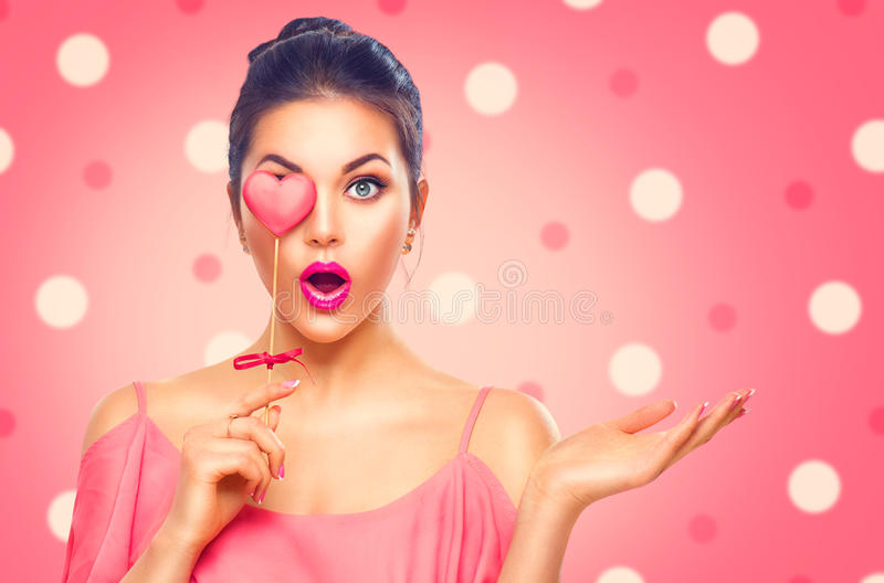 Valentine`s Day. Beauty model girl with Valentine heart shaped cookie. Valentine`s Day. Beauty surprised young fashion model girl with Valentine heart shaped royalty free stock image