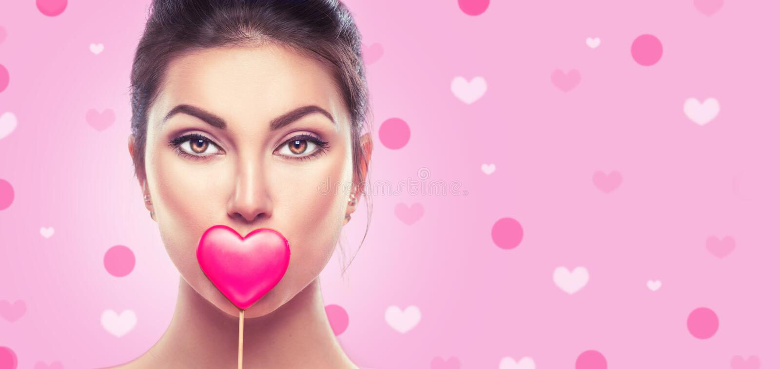 Valentine`s Day. Beauty young fashion model girl with Valentine heart shaped cookie over pink royalty free stock photography