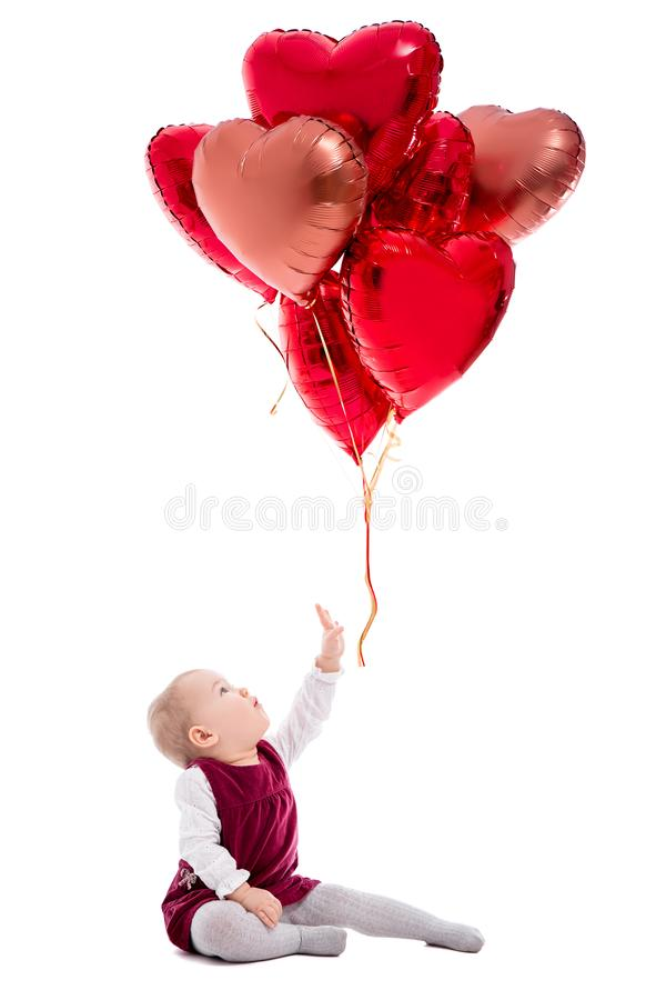 Valentine`s day or birthday concept - cute baby girl and flying red balloons isolated on white. Background royalty free stock photos
