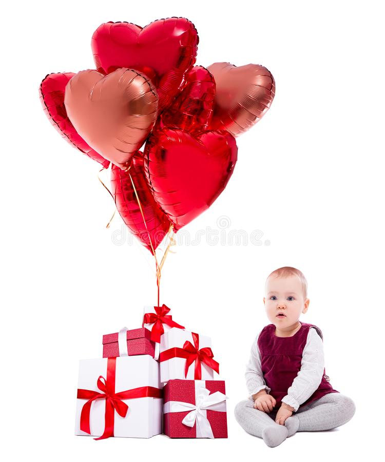 Valentine`s day or birthday concept - cute little girl, gift boxes and red balloons isolated on white royalty free stock image