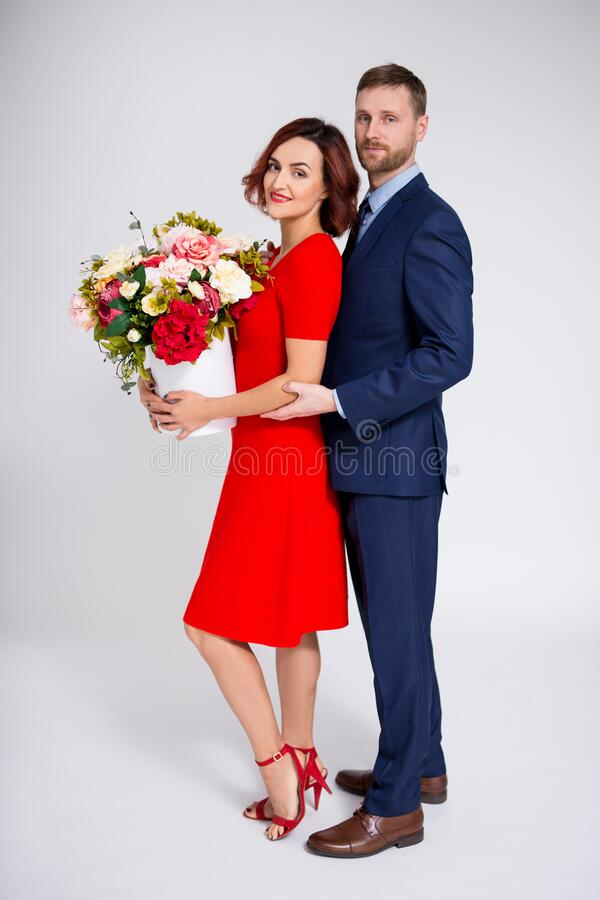 Valentine`s day or birthday surprise concept - handsome man surprising his girlfriend with flowers over white royalty free stock photography