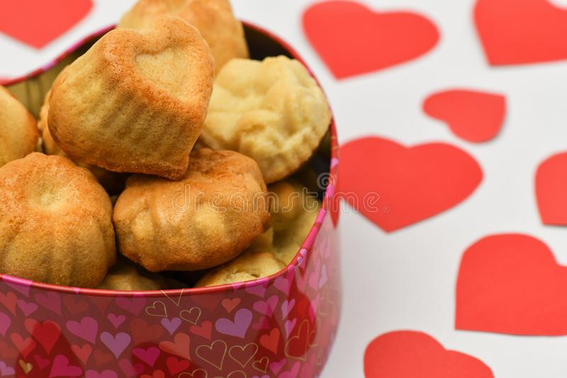 Valentine`s day. Box in the shape of a heart it has a lot of cakes, biscuits and cookies, near are a lot of red cut out hearts royalty free stock photography