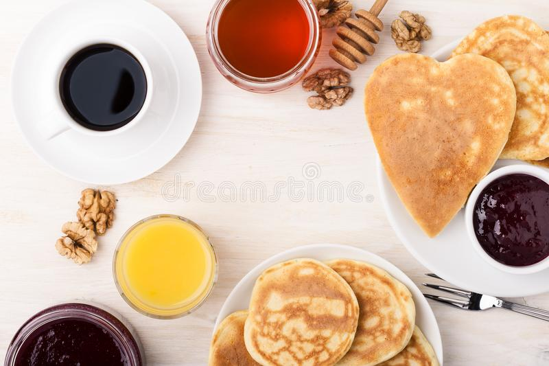 Valentine`s day breakfast or brunch. Table viewed from above. Valentine`s day breakfast or brunch. Homemade heart shape pancakes with berry jam and honey, orange stock photo