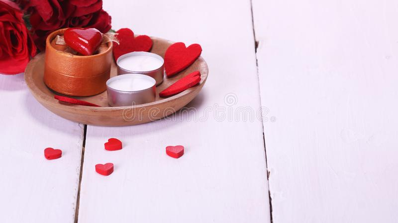 Valentine`s Day with candles, red roses, white table and red hearts stock image