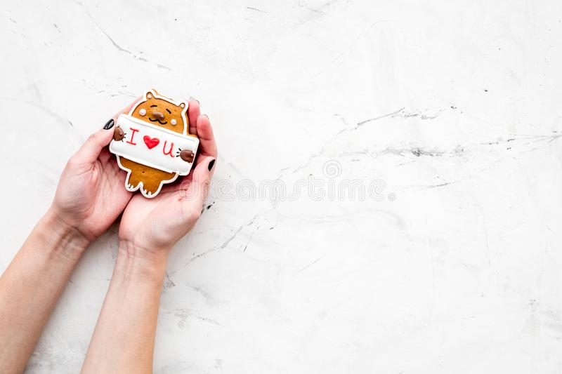 Valentine`s Day candy. Cookie in shape of bear with lettering I love you in hands on light grey background top view royalty free stock photography