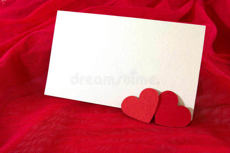 Valentine's day card. Blank Valentine's day card with two paper hearts on red fabric royalty free stock photos
