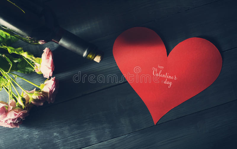 Valentine`s Day card with a bouquet of roses and a bottle of wine. Old blue wooden background with copy space stock images