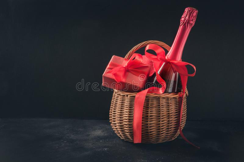 Valentine`s day card with champagne and gift hamper on black. Space for your greetings. Valentine`s day greeting card with champagne and gift hamper on black royalty free stock image