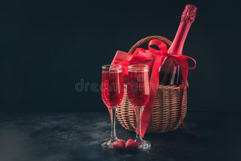 Valentine`s day card with champagne and gift hamper on black. Space for your greetings. Valentine`s day greeting card with champagne and gift hamper on black royalty free stock photography