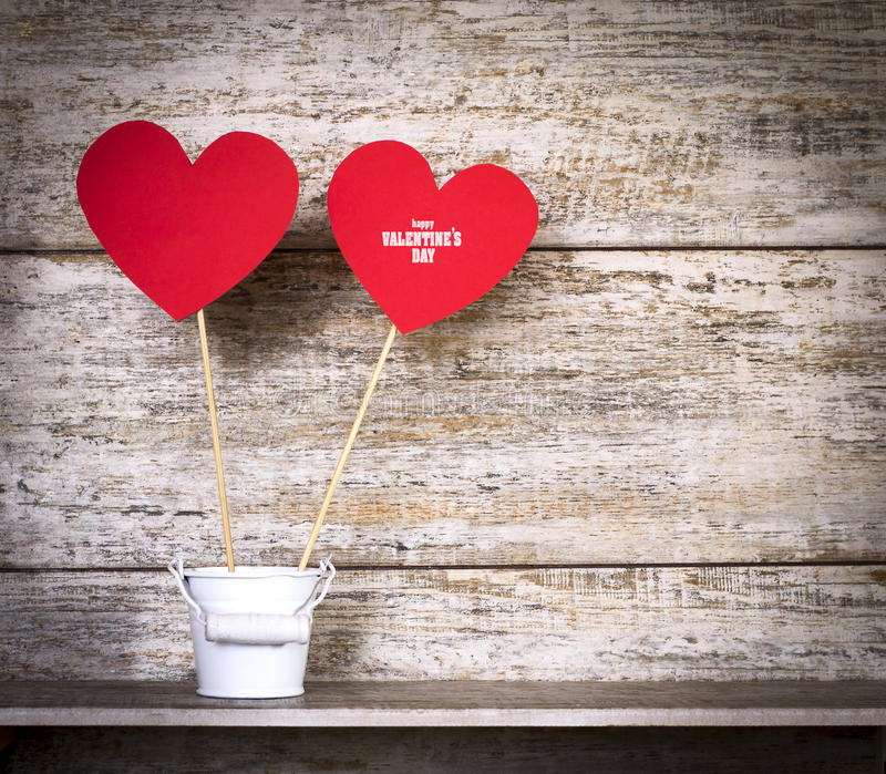 Valentine`s Day card with hearts on sticks in bucket. Valentine`s Day card with paper hearts on sticks in a bucket. With copy space. On a wooden background stock photos