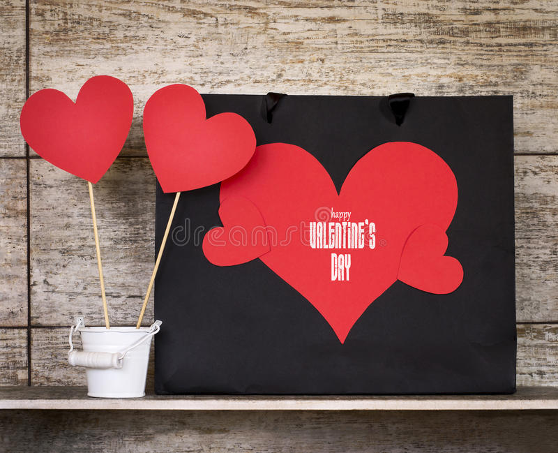 Valentine`s Day card with paper hearts and gift bags. stock photo
