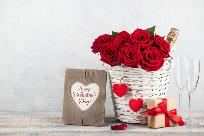 Valentine`s day card with red roses, gift box and champagne bottle royalty free stock images