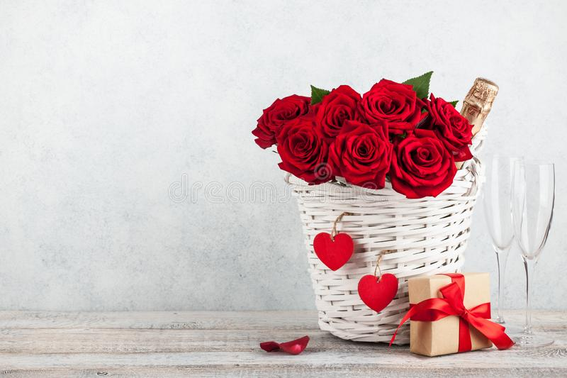 Valentine`s day card with red roses, gift box and champagne bottle royalty free stock photography
