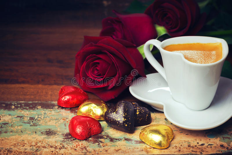 Valentine's day celebration with heart chocolate, coffee cup and roses on wooden background. Valentine's day celebration with heart chocolate, coffee cup and stock photography