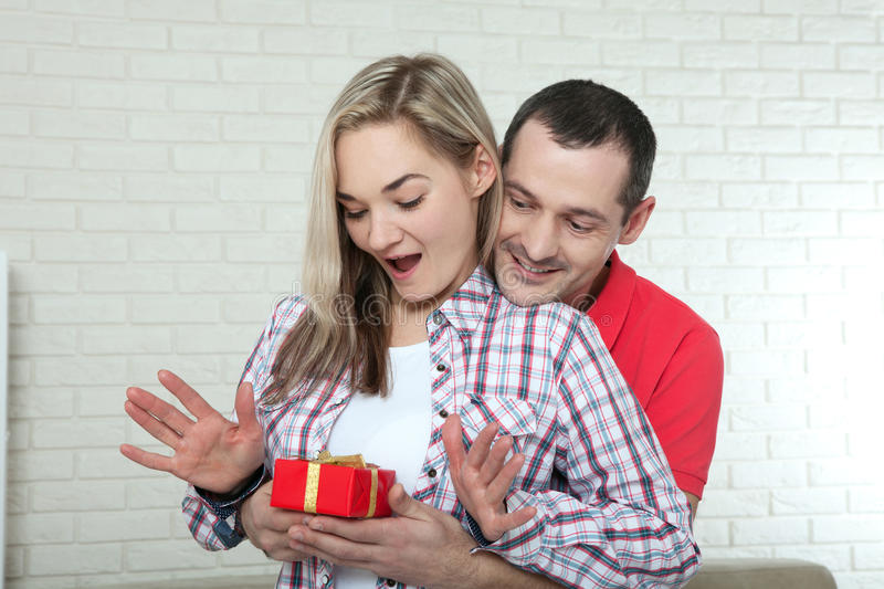 Valentine`s day or christmas concept - young woman opening gift stock photos