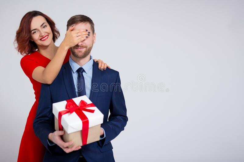 Valentine`s day, christmas or surprise concept - woman surprising her boyfriend with gift and copy space over white stock images