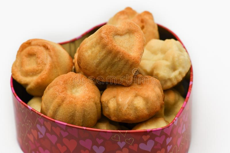 Valentine`s day. Closeup of delicious cupcakes in the shape of a heart in a beautiful box in heart shape on grey background. Macro photography royalty free stock image