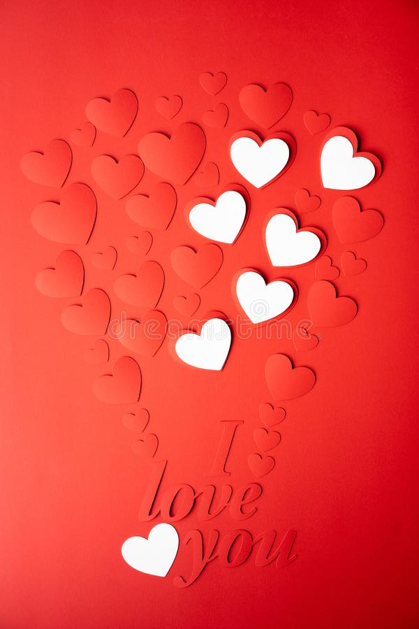 Valentine`s day concept. The background is red, the red hearts are cut out of paper. Words I love you royalty free stock image