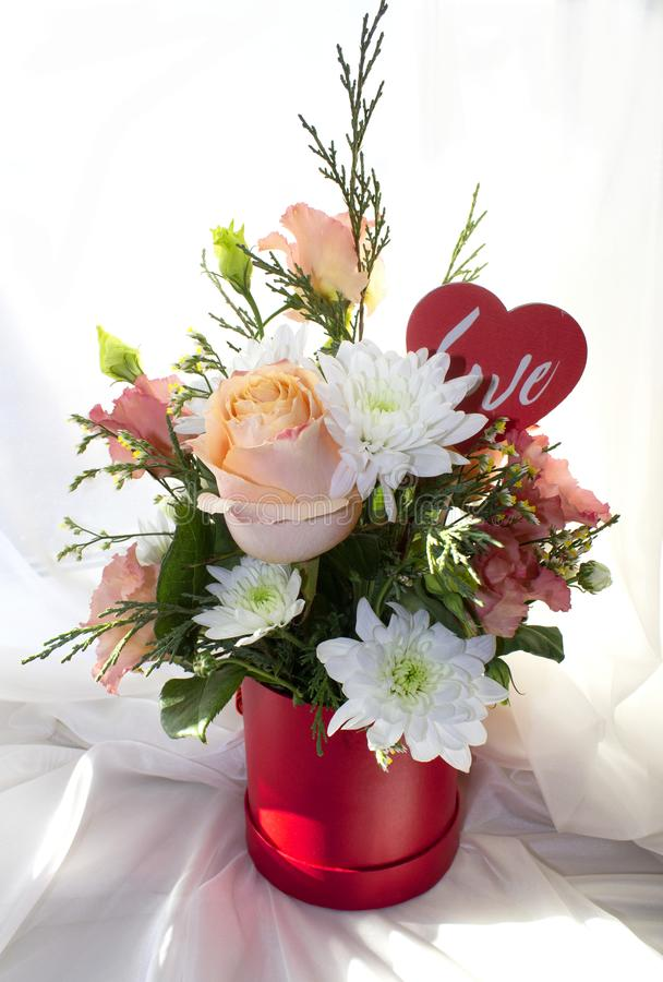 Valentine`s Day concept. Beautiful bouquet of flowers with heart shape sign stock images
