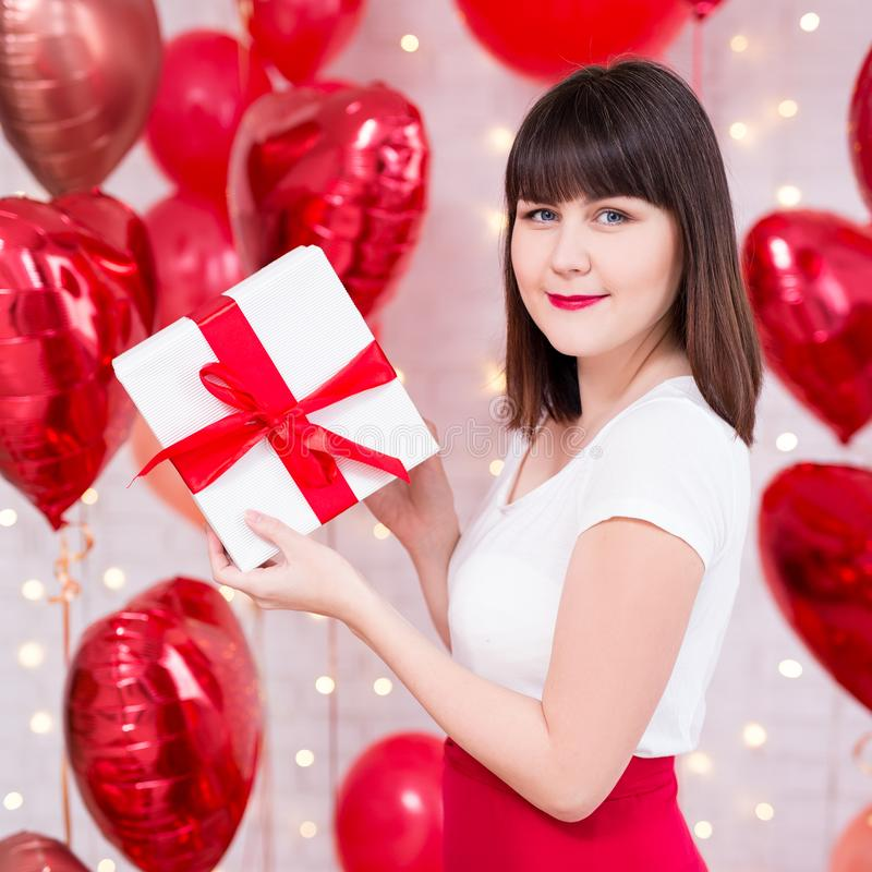 Valentine`s day concept - beautiful woman holding gift box over red balloons background stock photos