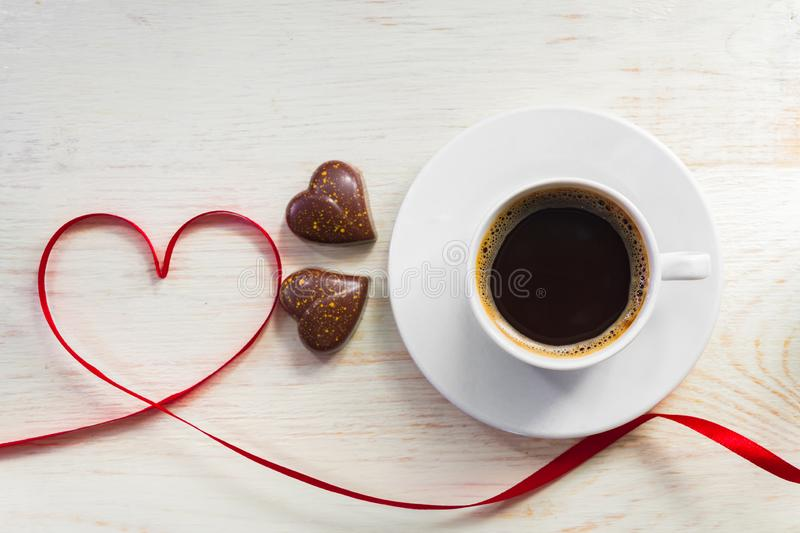 Valentine`s day concept with coffee cup, heart shape chocolate, and red ribbon on wooden background. Top view from above. Flat la stock photography