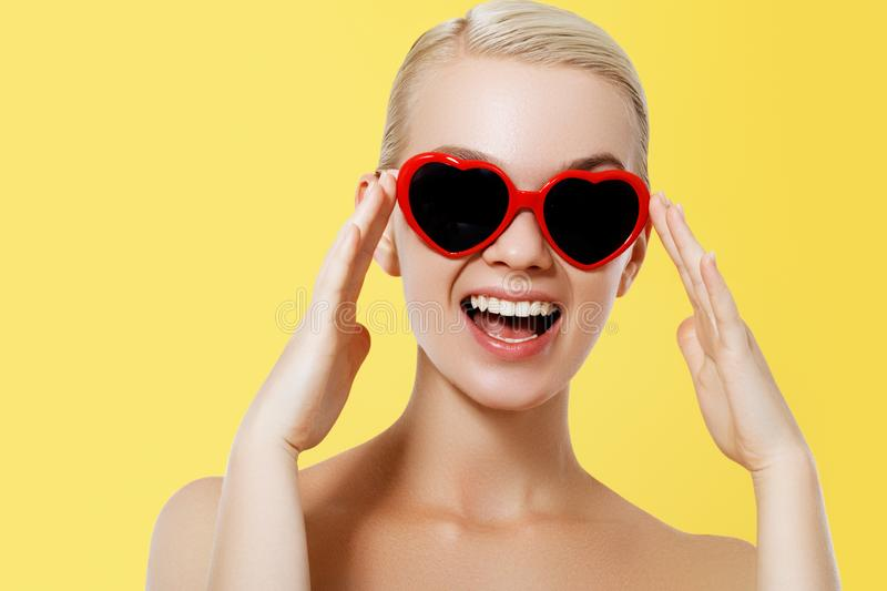 Valentine`s Day concept. Fashion Model girl isolated over yellow background. Beauty stylish blonde woman posing in heart stock photos