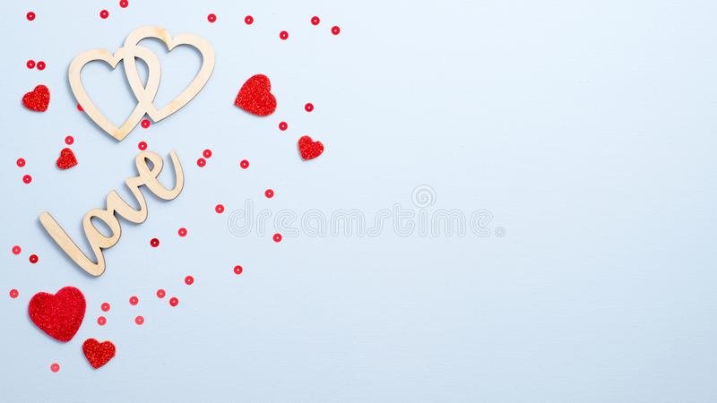 Valentine`s Day concept. Flat lay wooden sign. `Love` and hearts on blue background with red decor. Top view symbols of love for Happy Women`s, Mother`s stock photography