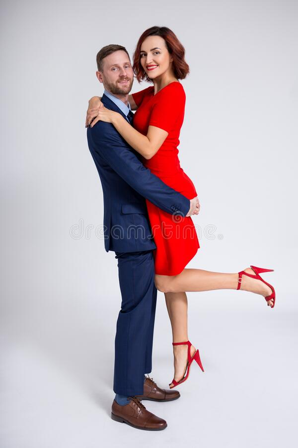Valentine`s day concept - full length portrait of handsome man holding beautiful woman in his hands over white royalty free stock photo