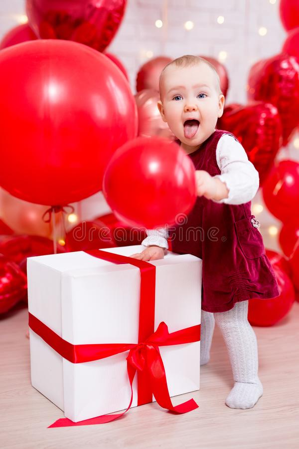 Valentine`s day concept - funny baby girl playing with red balloons and big gift royalty free stock photography