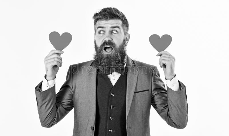 Valentine`s Day concept. Handsome man in formal suit giving red heart standing on white background royalty free stock image