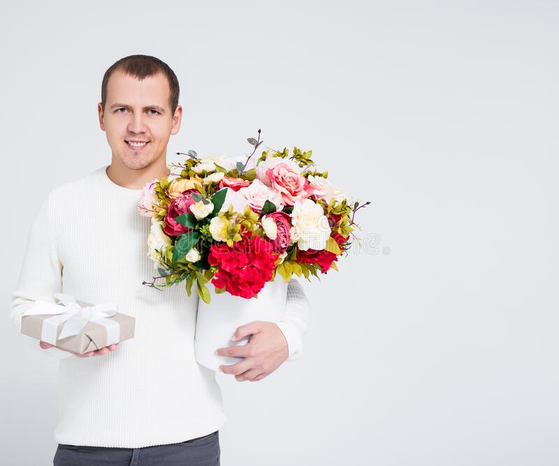Valentine`s day concept - handsome man in white warm sweater holding bouquet of flowers and gift box over gray background with royalty free stock image
