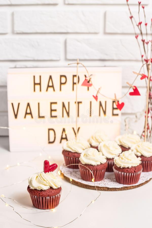 Valentine`s day concept. Happy Valentine`s Day is written on a decorative lamp next to red cupcakes. Red velvet with mascarpone cream. Valentine`s day concept royalty free stock image