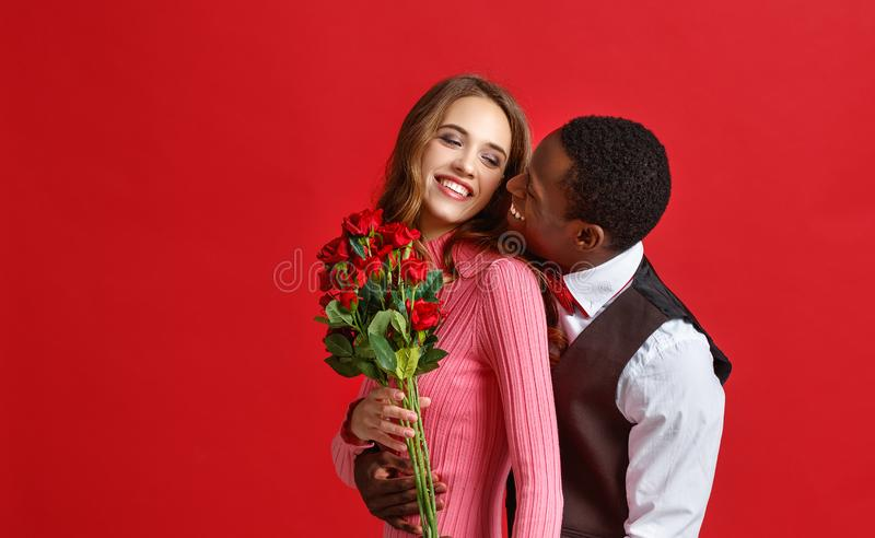 Valentine`s day concept. happy young couple with heart, flowers, gift on red. Background stock photos
