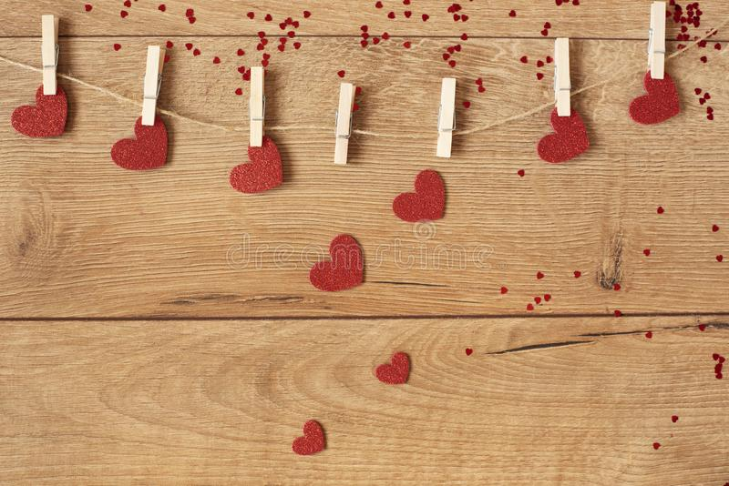 Valentine`s Day concept. Heart shape garland. Red glitter hearts hanging on rope on wooden background stock photos