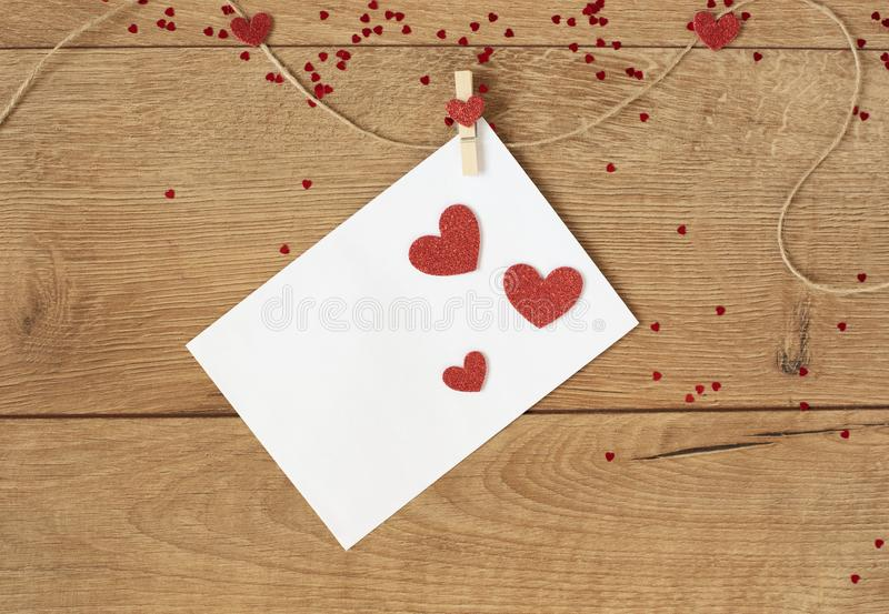 Valentine`s Day concept. Heart shape garland. Red glitter hearts and letter hanging on rope on wooden background royalty free stock photos