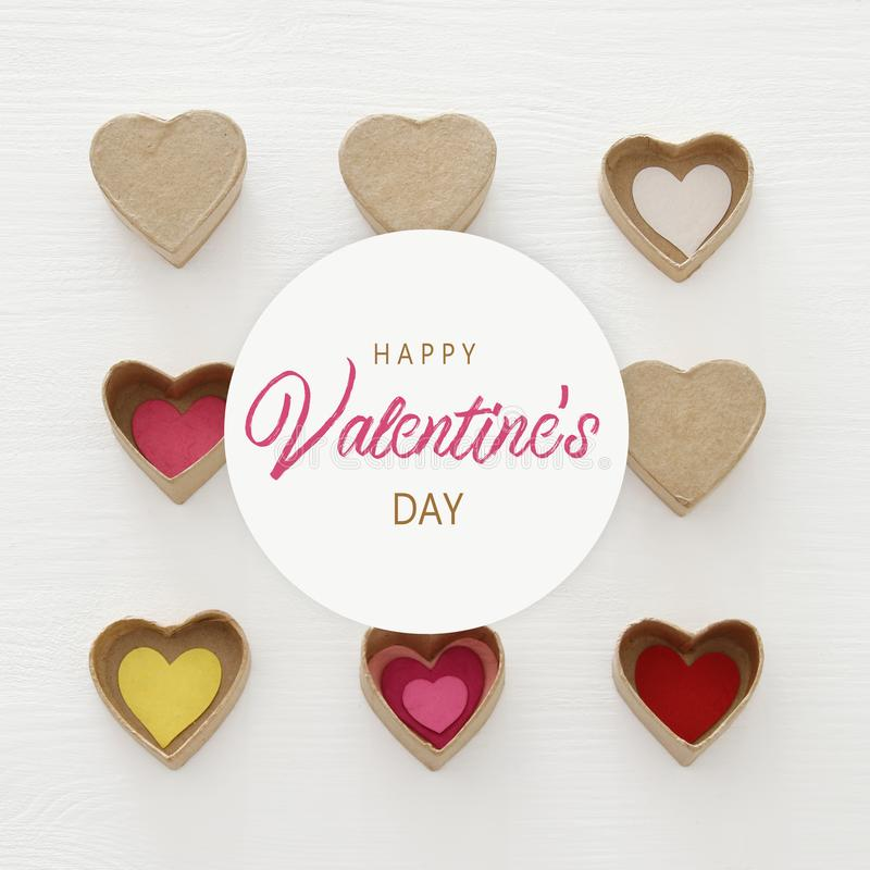 Valentine's day concept. hearts as paper gift boxes over wooden white background. vector illustration
