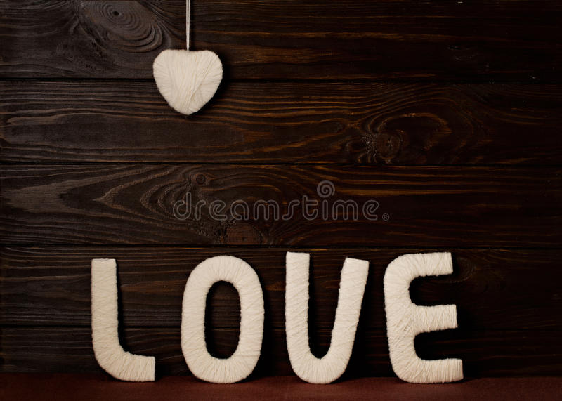 Valentine`s day concept. Letters LOVE and hearts made of yarn on stock image